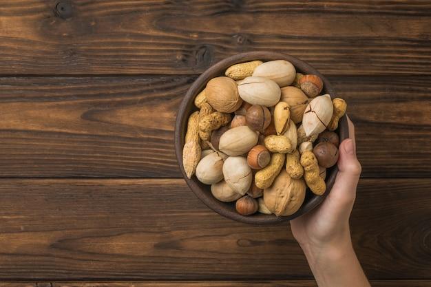 La mano di una donna tiene una ciotola piena di miscela di noci su un legno. cibo vegetariano.