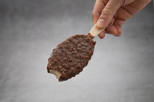 La mano di una donna tiene un bastoncino di ghiacciolo al cioccolato con un morso.