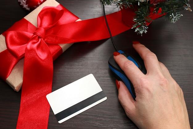 La mano di una donna tiene un mouse del computer. accanto a una carta di credito e un regalo con un fiocco rosso