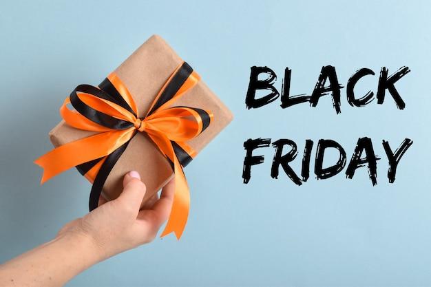 La mano di una donna tiene una confezione regalo con un nastro nero-arancio su sfondo blu. venerdì nero.