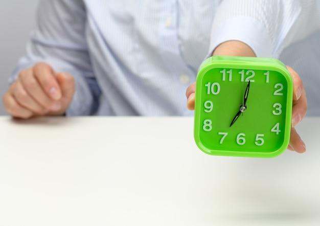 La mano della donna tiene una sveglia quadrata verde, l'orologio mostra le sette del mattino. sveglia presto, inizia la giornata