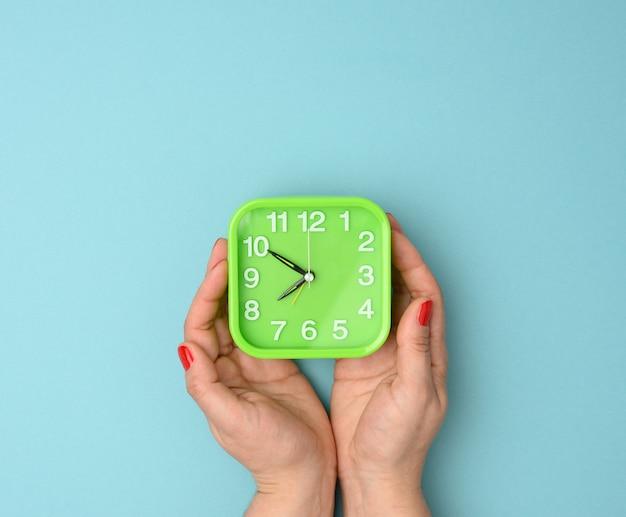 La mano della donna tiene una sveglia quadrata verde, il tempo è dalle dieci alle otto del mattino. concetto di ascesa precoce, sfondo blu