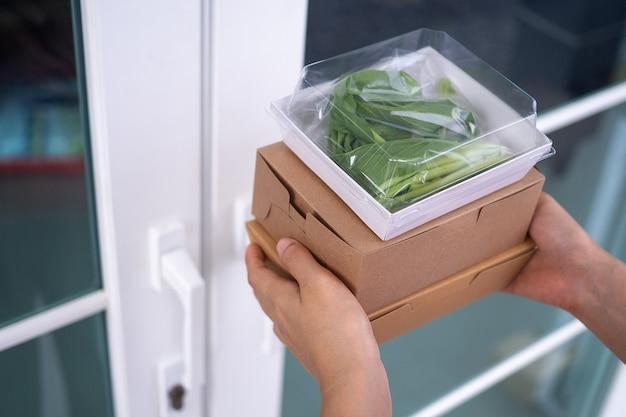 La mano di una donna tiene un cestino per il pranzo dopo aver chiamato un ordine online tramite un'app con un servizio di consegna a domicilio. giovane donna che trasporta scatole di cibo da asporto.