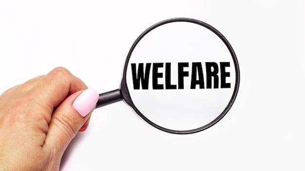 La mano della donna tiene una lente d'ingrandimento con la scritta welfare