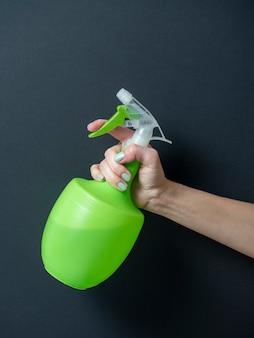 La mano di una donna tiene una bottiglia di plastica con un flacone spray verde su sfondo nero. il concetto di assistenza domiciliare e pulizia. foto verticale
