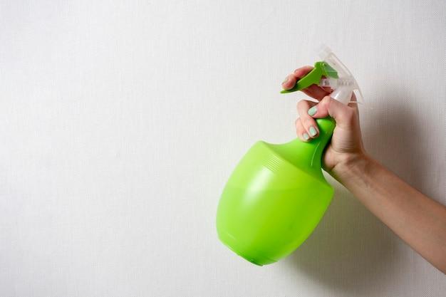 La mano di una donna tiene una bottiglia di plastica con un flacone spray verde su sfondo grigio. il concetto di assistenza domiciliare e pulizia. copia spazio
