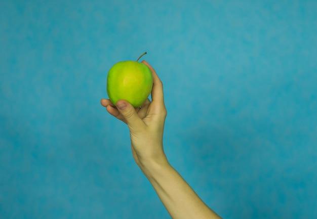 La mano di una donna tiene una mela matura su sfondo blu.