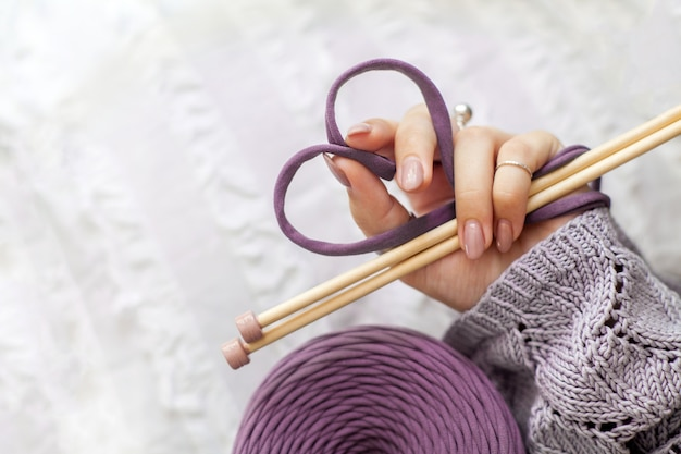 La mano di una donna tiene un filo di maglia viola, piegandolo a forma di cuore. concetto di amore per il lavoro a maglia e l'artigianato.