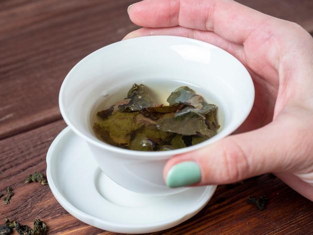 La mano di una donna tiene una ciotola di porcellana bianca con il tè. fondo in legno. le foglie aperte del tè a foglia larga. tè cinese. festa del tè