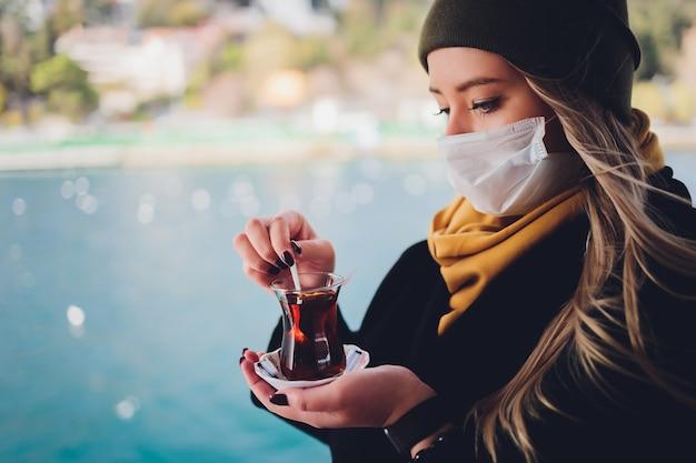 La mano di una donna è in possesso di una tazza bianca di bevanda calda a base di latte con cannella chiamato turco salep sahlep sullo sfondo di acqua increspata e nebbiosa torre della fanciulla in lontananza, istanbul