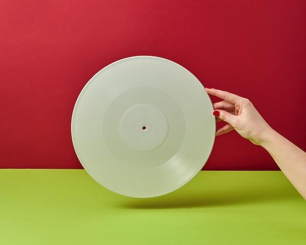 La mano della donna sta tenendo un record audio in vinile bianco su uno sfondo verde rosso bicromia con una copia