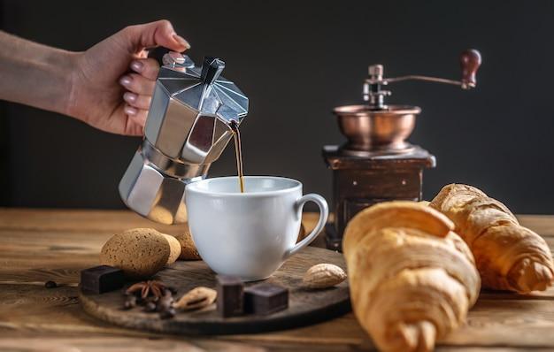 La mano di una donna sta versando caffè nero caldo fresco da una caffettiera geyser