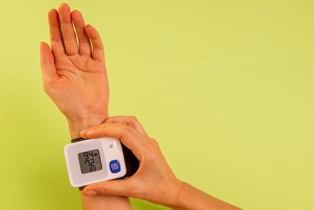Mano della donna che misura la sua pressione sanguigna.