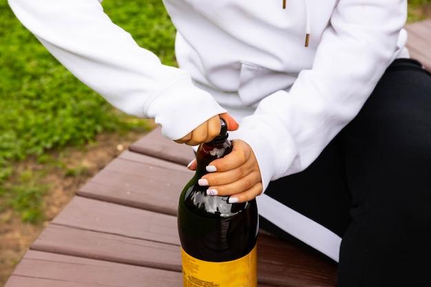 La mano della donna apre il tappo di una bottiglia con una bibita analcolica