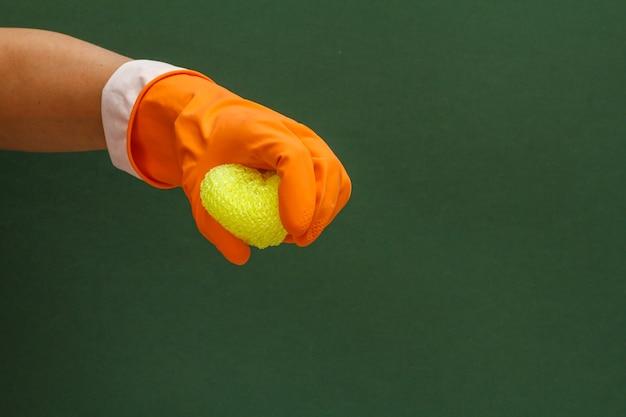 Mano della donna in guanto protettivo arancione con spugna in uno sfondo verde. concetto di lavaggio e pulizia.