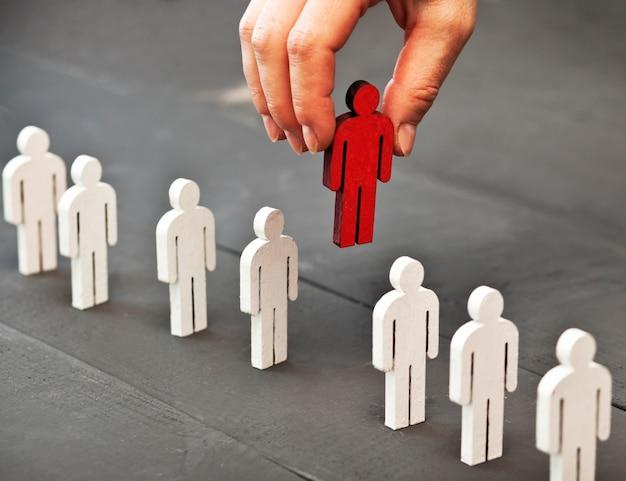 La mano della donna prende una persona rossa di legno dalla fila di un'altra