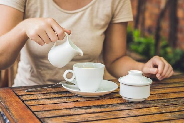 Mano della donna che versa il latte in una tazza di caffè bianca nella caffetteria all'aperto
