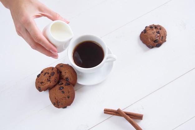 La mano di una donna versa il latte nel caffè. una tazza di caffè profumato con cannella e biscotti su uno sfondo bianco. vista dall'alto.