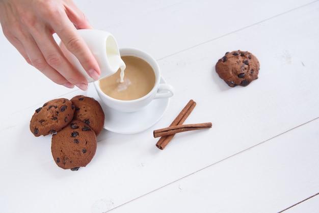 La mano di una donna versa il latte nel caffè. una tazza di caffè profumato con cannella e biscotti su uno sfondo bianco.