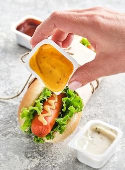 La mano di una donna versa la senape su un hot dog. fast food.