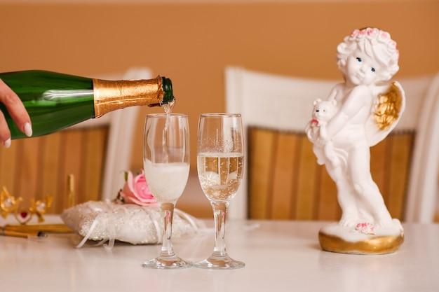La mano della donna versa lo champagne di nozze in bicchieri da una bottiglia a una celebrazione, matrimonio.