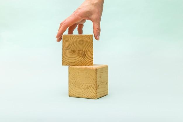 La mano della donna mette il cubo di legno in bianco uno sopra l'altro.