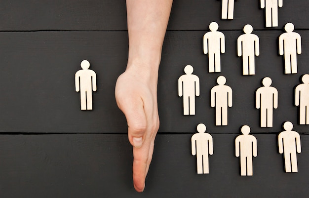 La mano della donna separa un persnon di legno dal gruppo di altri.