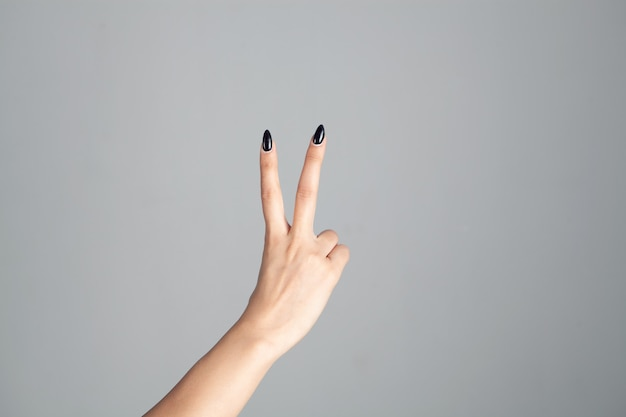 La mano della donna che mostra il segno di pace