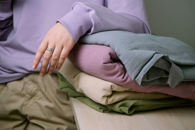 Mano della donna sulla pila di tessuto color pastello