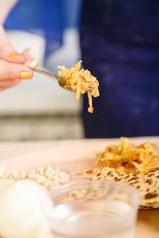 La mano di una donna al tavolo per il seder pasquale sta mangiando un choroset. foto verticale
