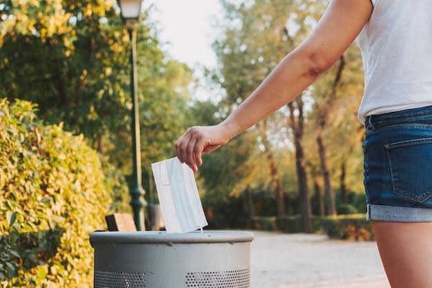 La mano di una donna che lancia una mascherina medica nel cestino della carta di un parco.