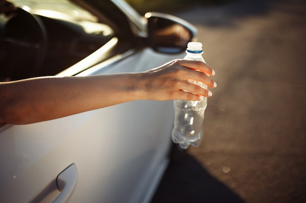 La mano di una donna che lancia una bottiglia di plastica dal finestrino dell'auto.
