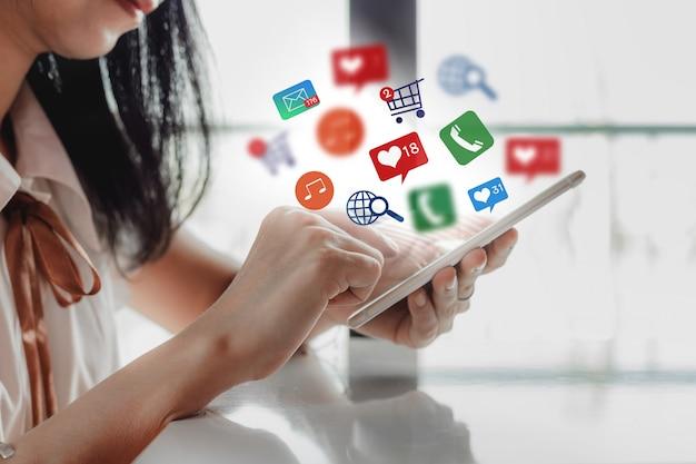 La mano della donna facendo uso dello smartphone con le icone di notifica per il concetto sociale di tecnologia e di media