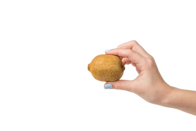 La mano di una donna con una manicure blu tiene un kiwi isolato su una superficie bianca