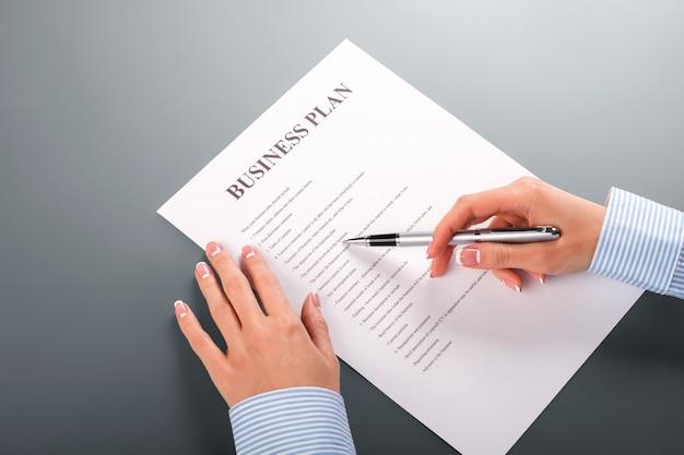 Mano della donna con il business plan. il business plan della dipendente. breve e chiaro. scegliere la giusta strategia.
