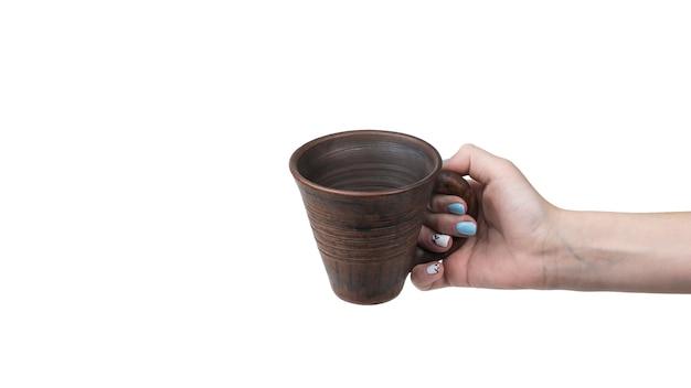 Mano di una donna con una tazza di argilla isolata su una superficie bianca