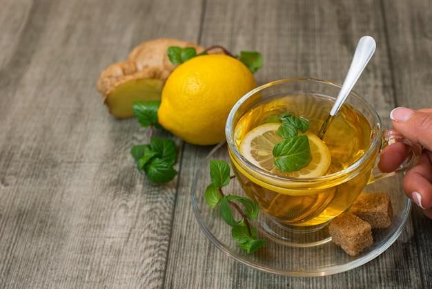 La mano della donna con la tazza di tè allo zenzero, zucchero bruno lemonnd su legno grigio