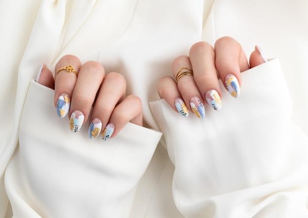 La mano della donna con le unghie alla moda che tengono il tessuto