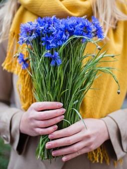 Mano di donna con fiori, bouquet di fiordaliso sulla mano femminile