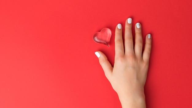 La mano di una donna con una manicure leggera tiene un cuore di vetro su uno sfondo rosso. un simbolo di amore e vita.
