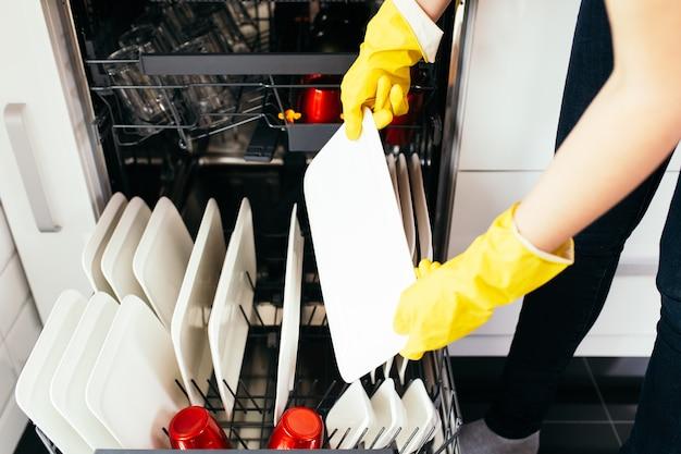 La mano della donna con una lavastoviglie aperta piena di piatti puliti.