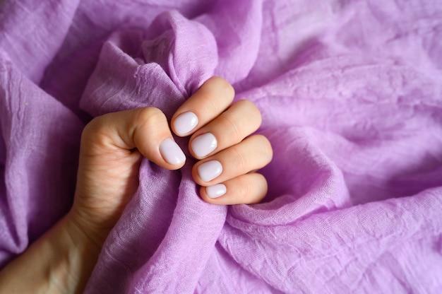 La mano della donna con le unghie dipinte viola pallido regge un tessuto di cotone lilla su uno sfondo di tessuto lilla