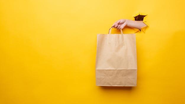 La mano di una donna con un sacchetto di carta su sfondo giallo