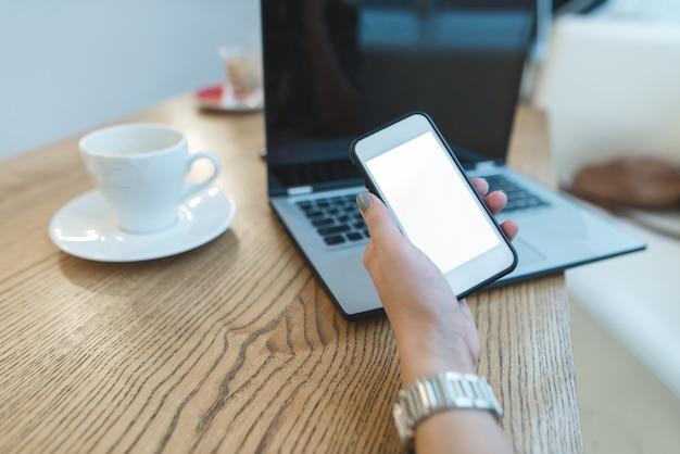 La mano della donna con il telefono a disposizione contro il computer portatile e il caffè