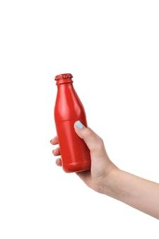 La mano di una donna con una bottiglia chiusa di vetro rossa isolata su una superficie bianca