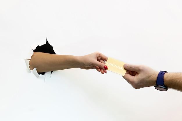 La mano di una donna con una manicure rossa passa una carta di credito d'oro a un uomo attraverso carta bianca strappata. mano attraverso carta bianca strappata