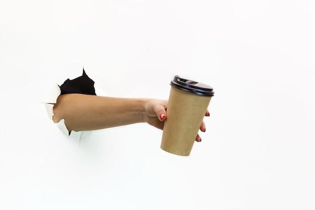 La mano di una donna con la manicure rossa attraverso la carta bianca strappata tiene una tazza di caffè di carta. mano attraverso carta bianca strappata. mano che tiene il bicchiere di carta