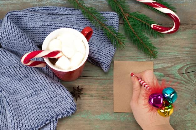 La mano della donna che scrive una lettera su uno sfondo di legno con decorazioni natalizie.