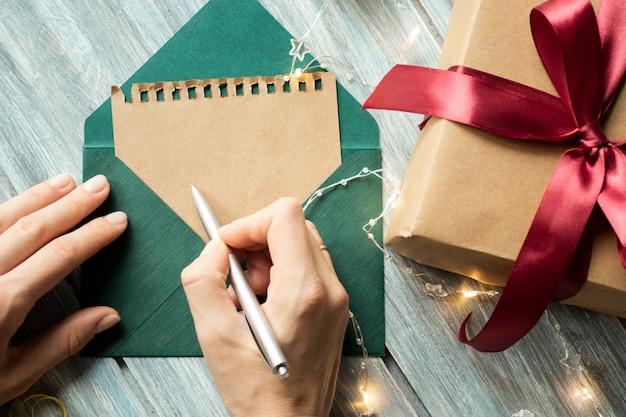 Mano della donna che scrive in taccuino decorato con decorazioni natalizie