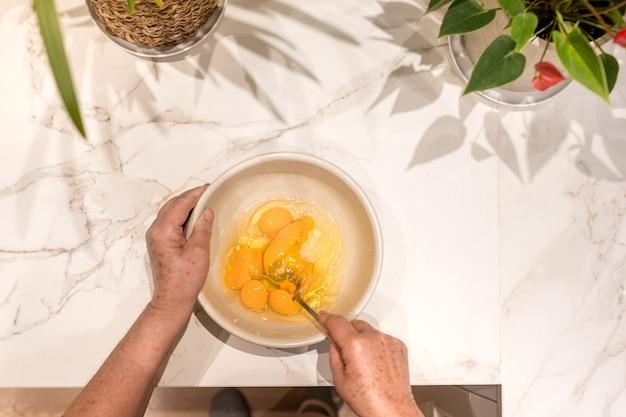 Mani di una donna che sbattono le uova in una ciotola in una cucina bianca